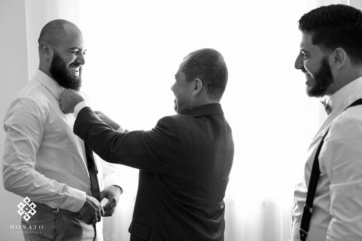 o pai e o irmão ajudam o noivo douglas se arrumar, na preparação para a cerimonia.