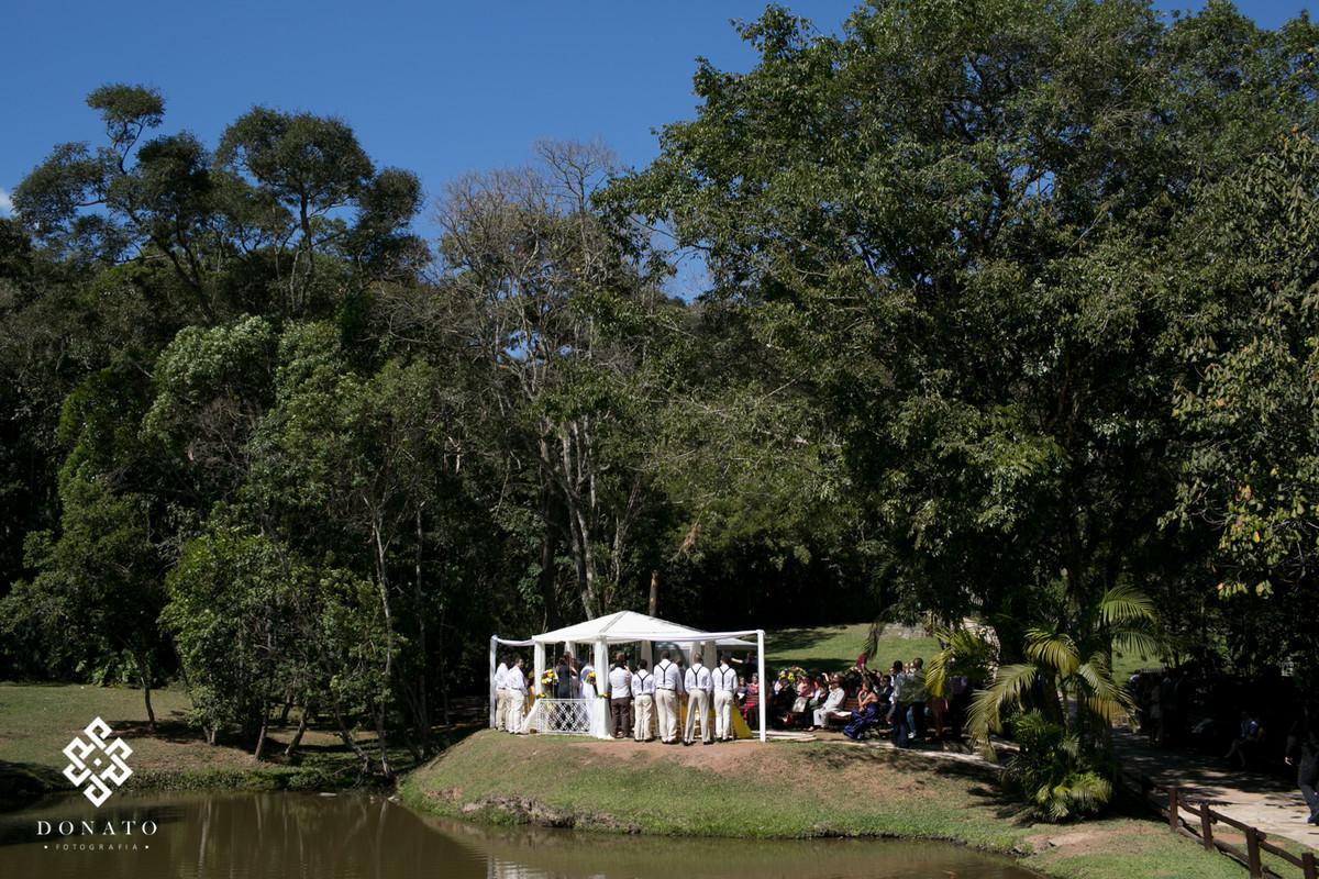 Visão geral da cerimonia do espaço natureza, com todos os padrinhos perfilados, na paisagem tem um gazebo todo branco entre grandes arvores e um lindo lago.