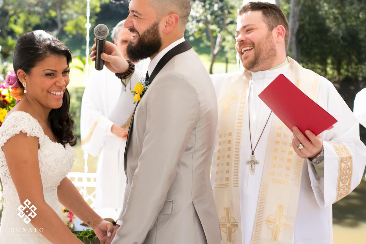 Noivos dao risada, eles estão se olhando ao fundo o reverendo lucas também ri da situação.