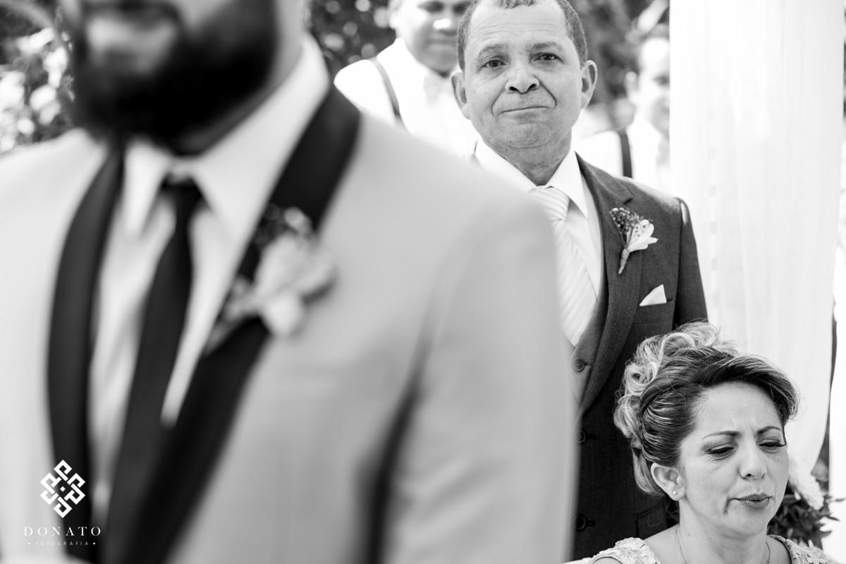 Pai e mãe do noivo se emocionam ao ver o filho se casando.