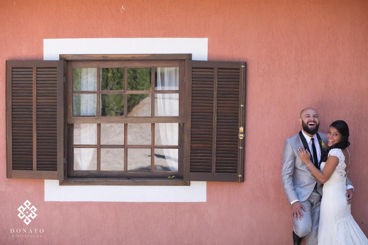 Noivos namoram em frente a janela do espaço natureza, a parede de cor salmão da um efeito legal a foto.