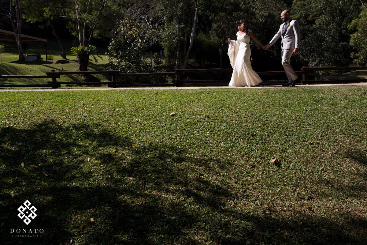 Noivos caminham em frente ao lago, com destino a festa, o lago do espaço natureza ao fundo da a imagem um charme.