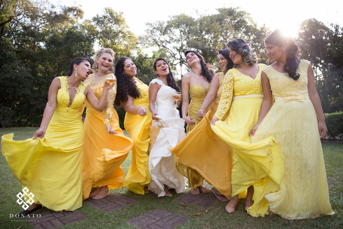 A noiva e as madrinhas brincam com o vestido, todas as madrinhas com vestidos amarelos deixa um efeito bem legal a imagem.