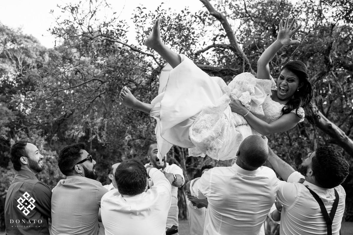 A noiva é jogada pra cima, ela esta de lado e muito alegre, congelado no ar, paresse que o tempo parou e ela esta flutuando na alegria.