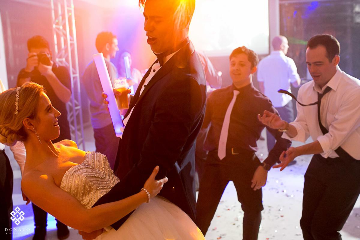 noivo dança com a noiva, com uma luz meio alaranjada.