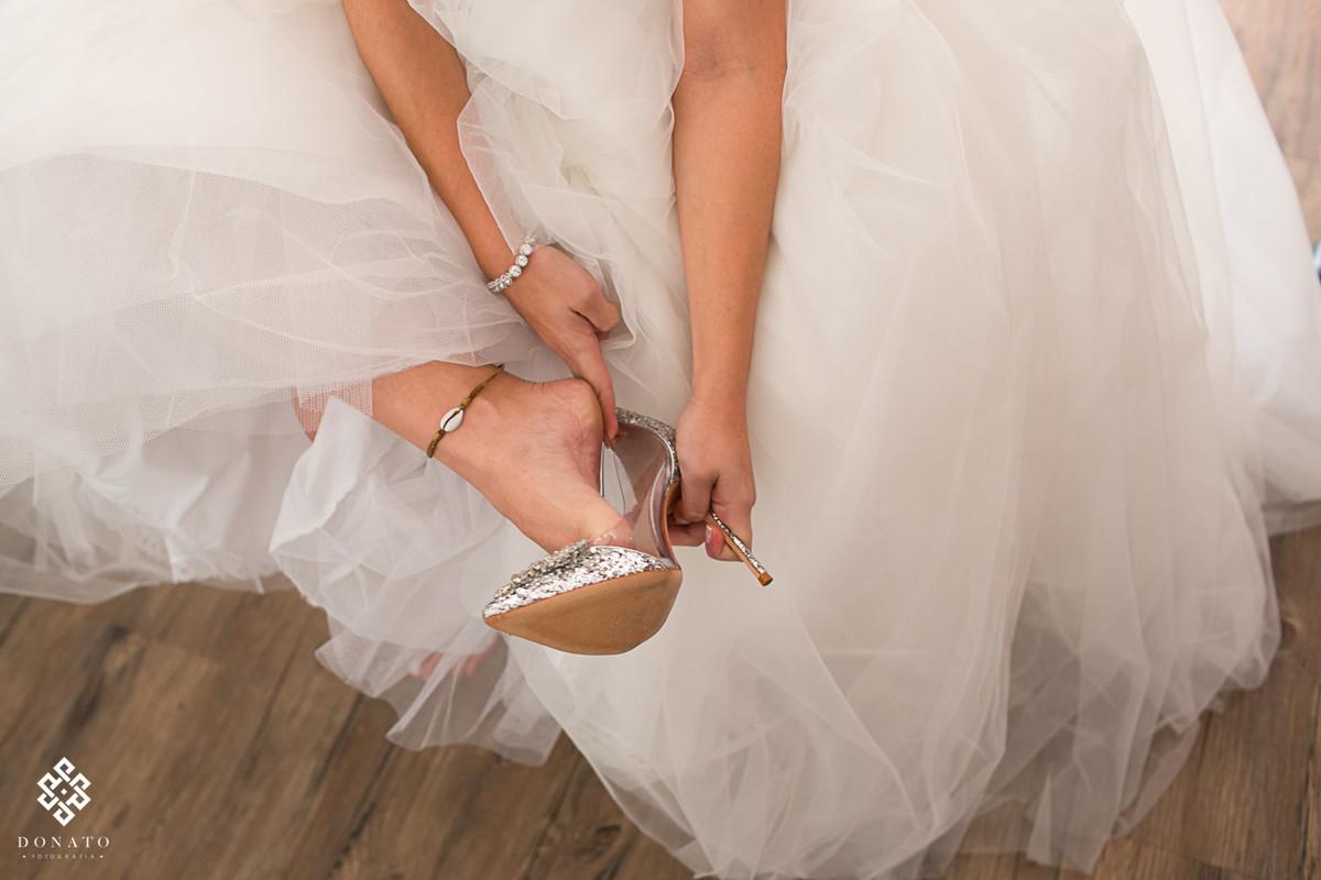noiva coloca o sapatos pronta para ir para o altar.