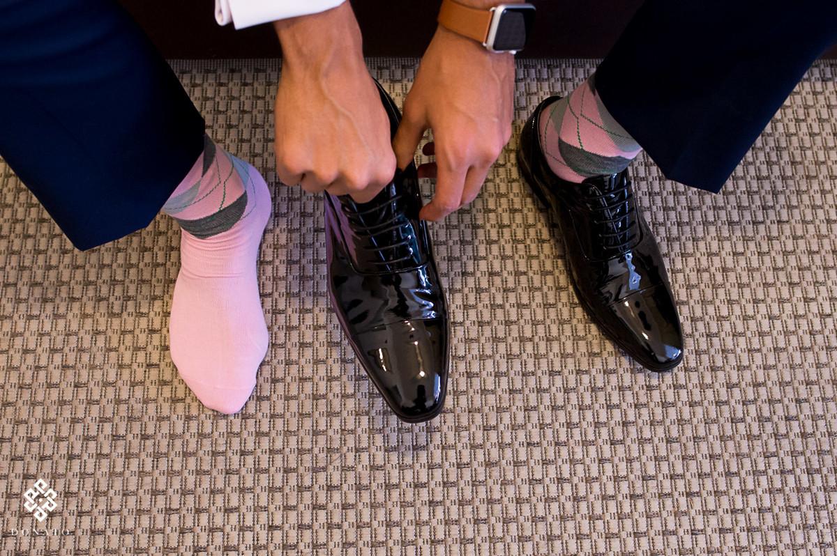 detalhe do sapato e meias do noivo, a meia cor de rosa da todo um charme e modernismo a foto.