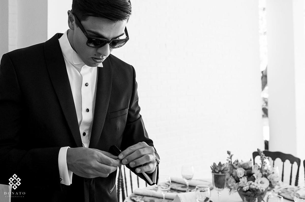 noivo de oculos escuro arruma os detalhes da festa.