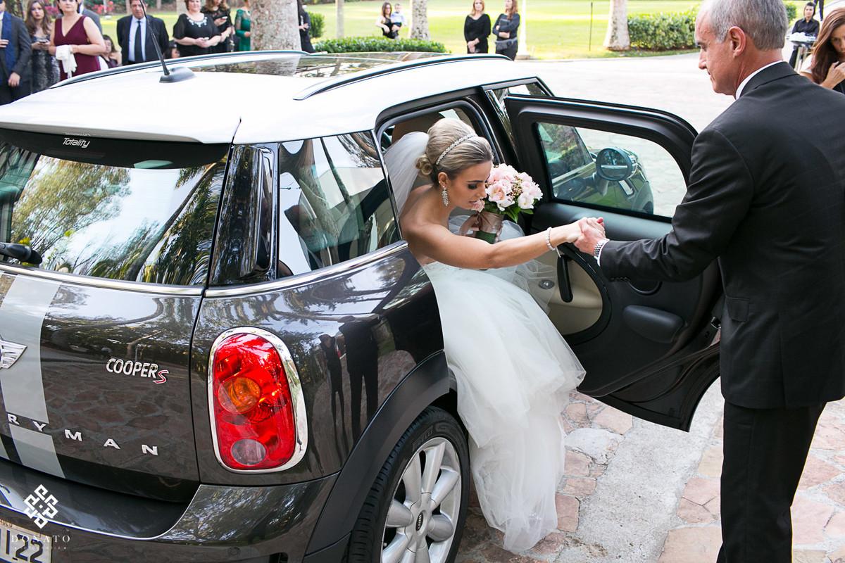 pai ajuda a noiva sair do mini coupe, para entrar na cerimonia.