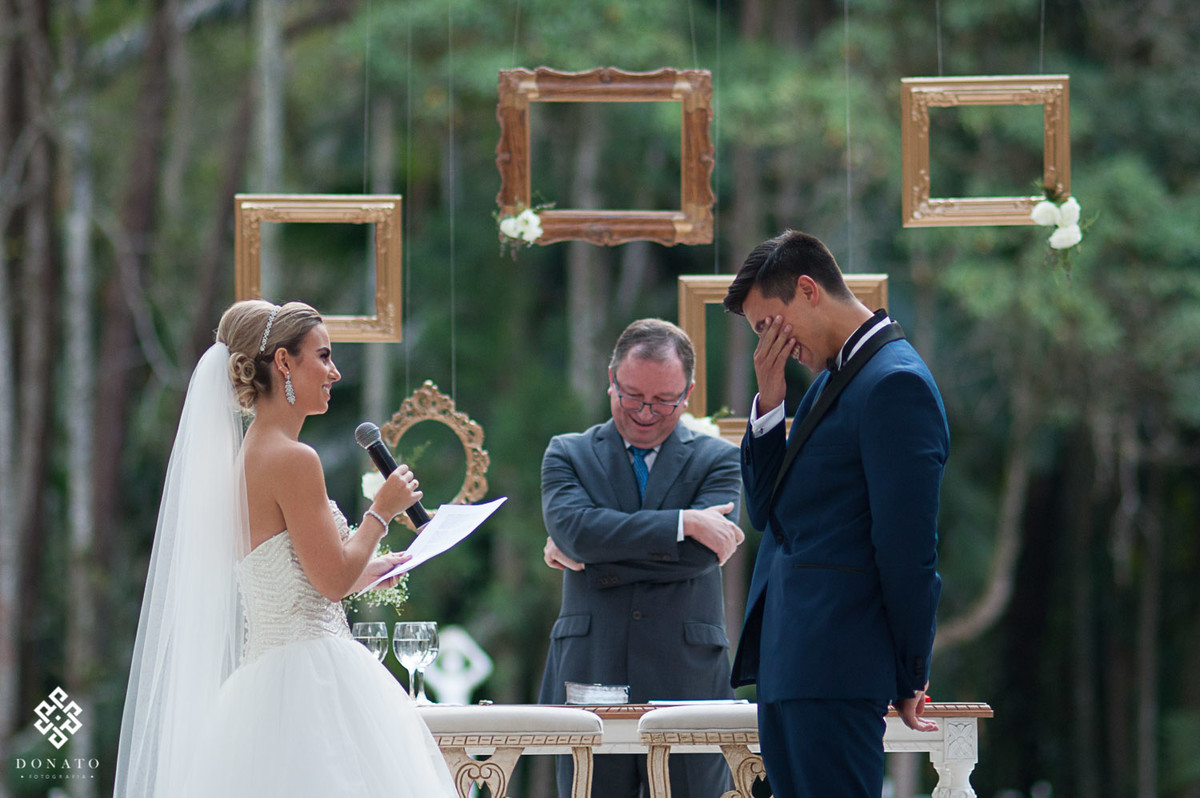 noivo jora emocionado nos votos, a noiva esta falando no microfone e o pastor rindo atrás.