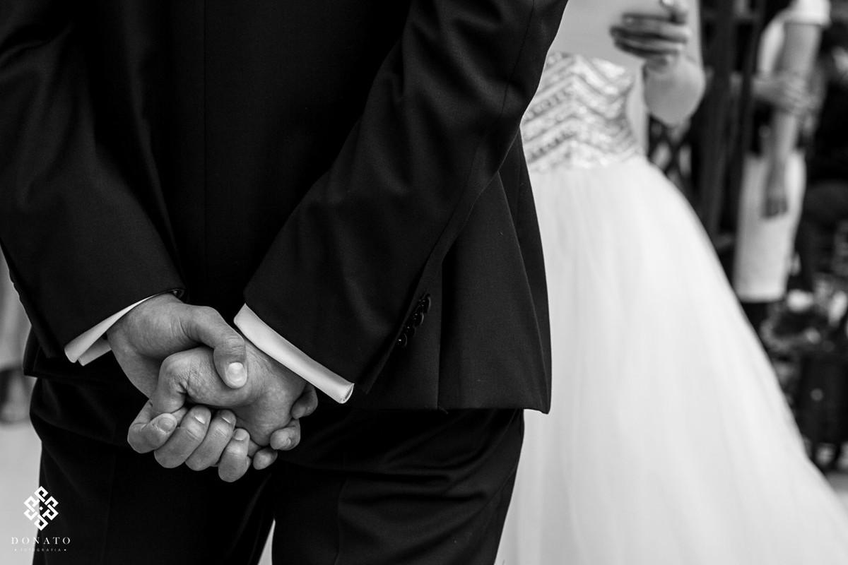 detalhe das mãos do noivo fechada e para trás, dando o sinal que esta tenso e nervoso.