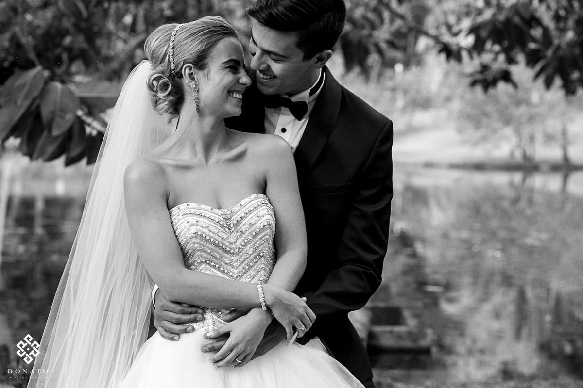 noivos namoram no jardim, bem abraçadinhos, foto esta em branco e preto.