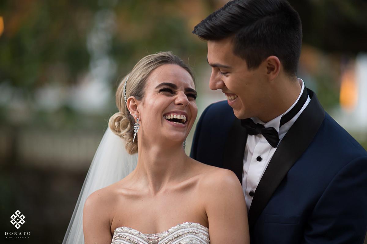 noiva se diverte e da um largo sorriso, enquanto é abraçada pelo noivo.