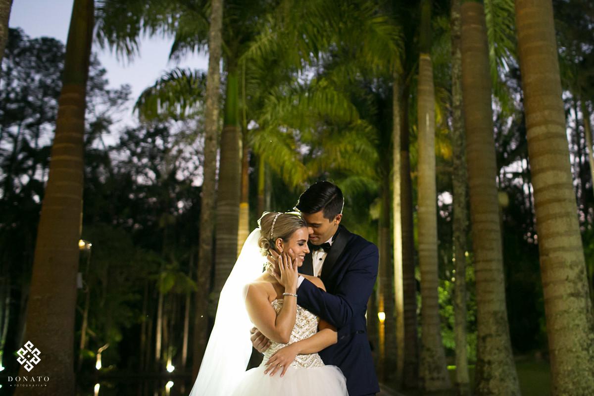 noivos namoram em frente as imensas palmeiras da fazenda 7 lagoas.