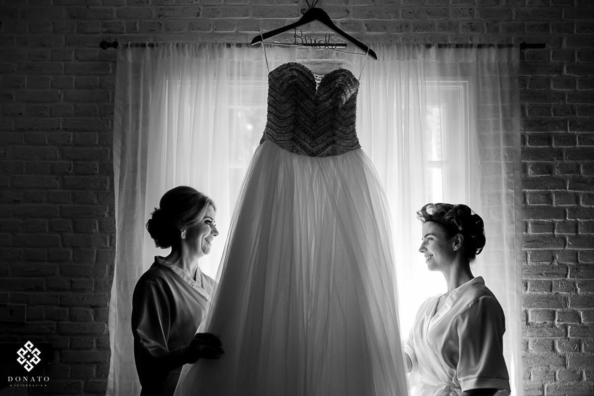 noiva com a mãe, olham os ultimos detalhes do vestido.