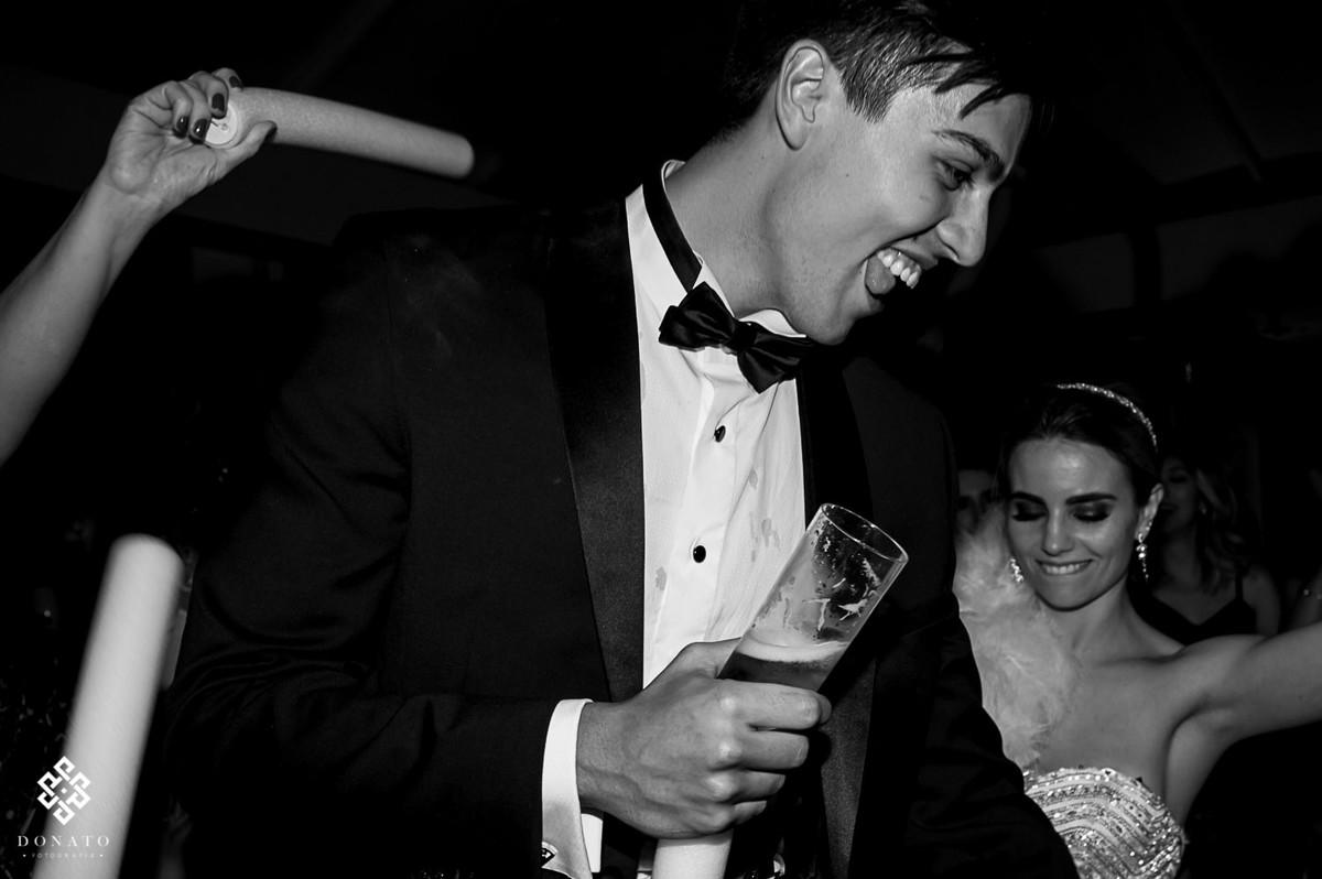 noivo dança com um copo de cerveja na mão.