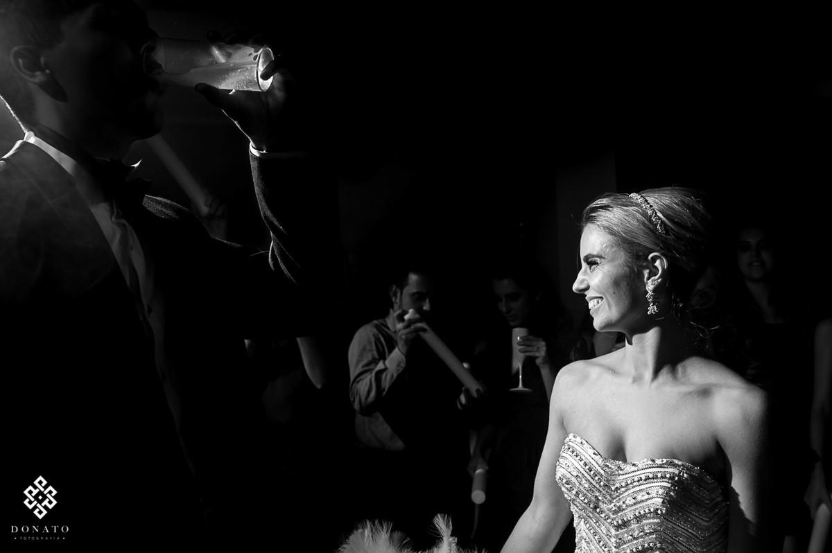 noivo toma um copo de cerveja e a noiva se diverte ao fundo.