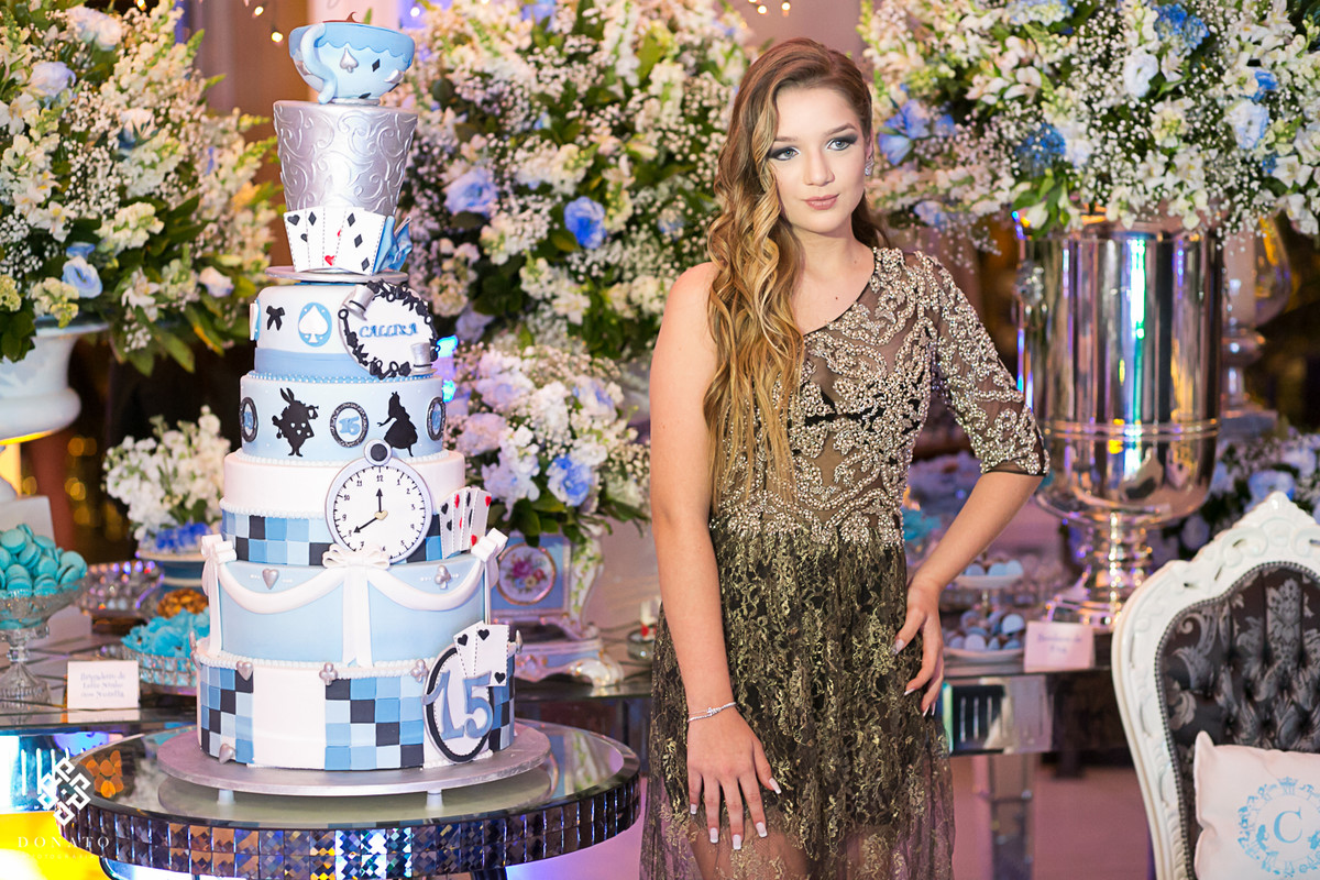 aniversariante pronta para receber os convidados, esta em frente ao bolo tematico com detalhes da alice no pais das maravilhas