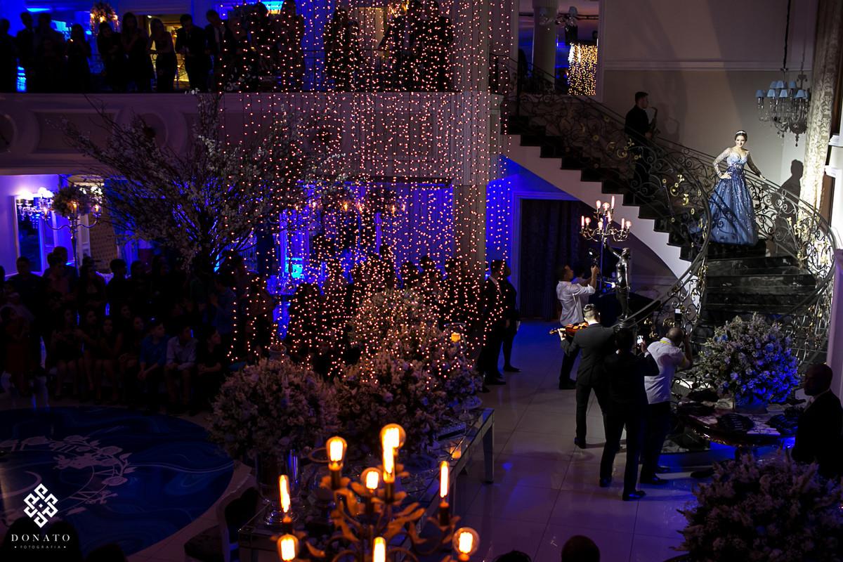 aniversariante desce por escadaria do buffet kristian platz, um veo de luzes deixa tudo mais lindo ainda.
