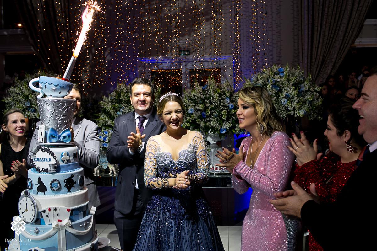 hora do parabéns, a frente o bolo lindo com o tema alice, e ao fundo todos muito animados cantando parabéns.