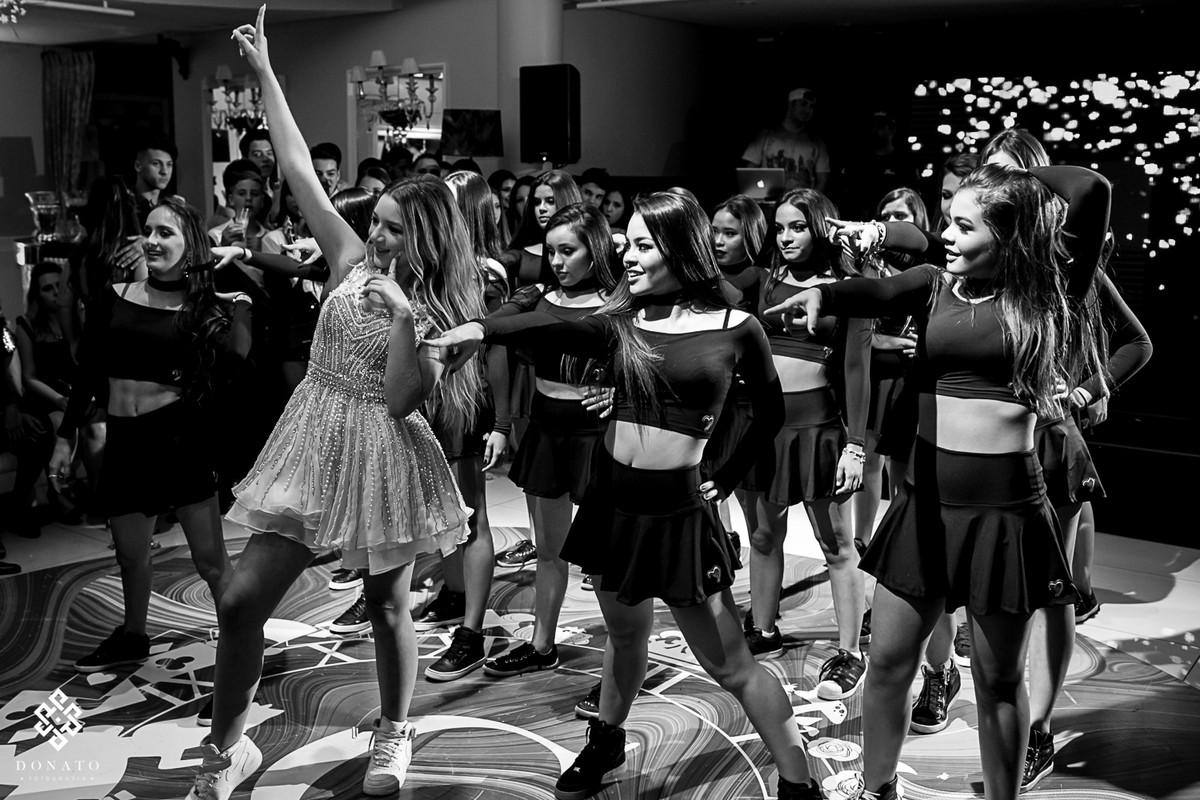 amigas dançam junto com a debutante, ela lidera a dança a frente, ela esta de branco e as amigas de preto.