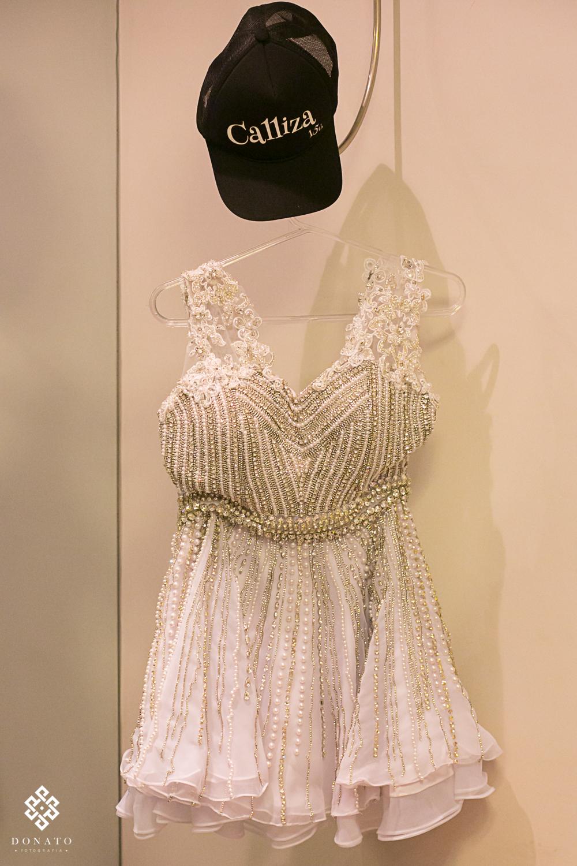 vestido da balada, pendurado em um cabide, junto com um boné personalizado com o nome da debutante.