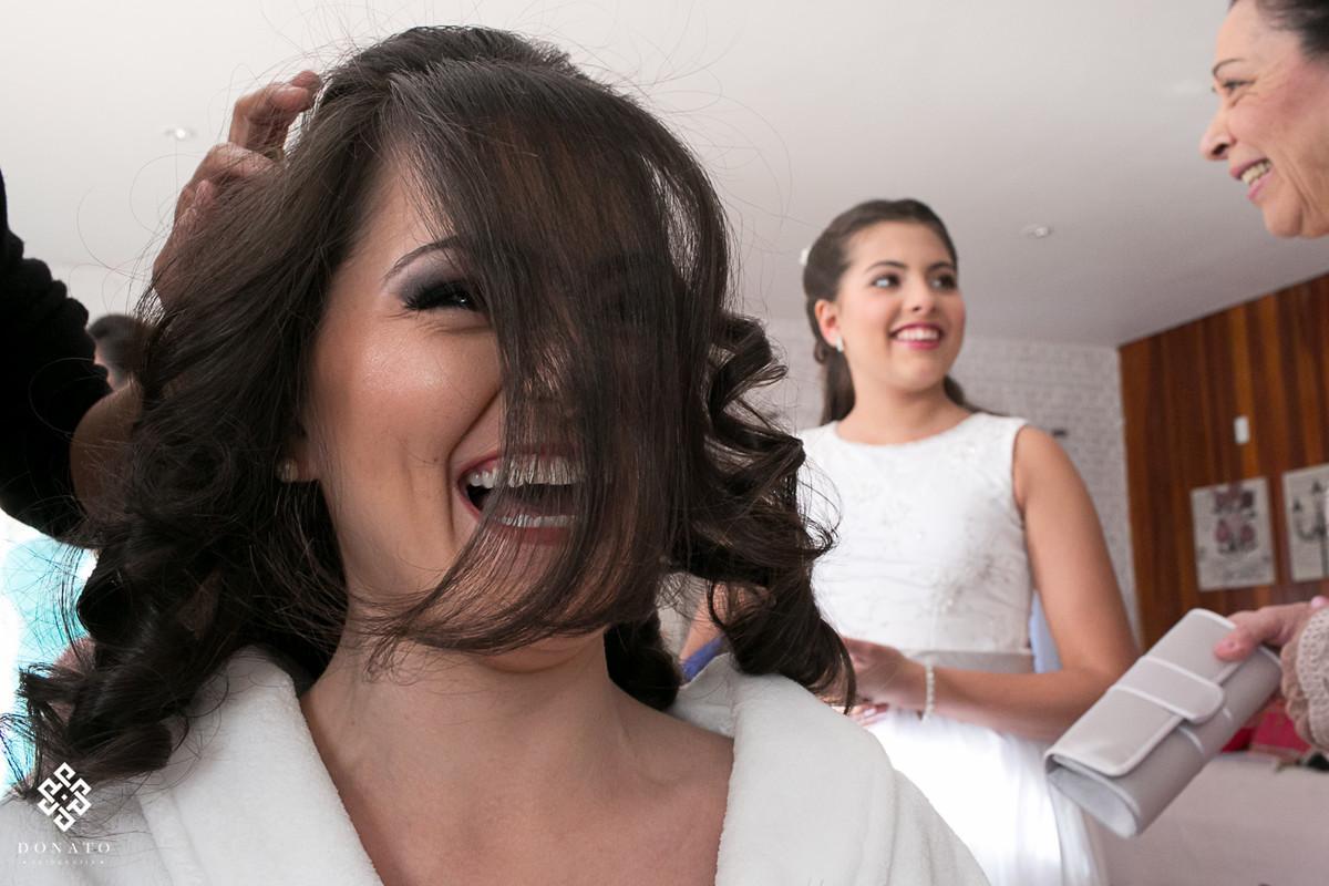 noiva se diverte enquanto seu cabelo esta sendo arrumado, a linda franja e seu sorriso deixam a imagem linda.