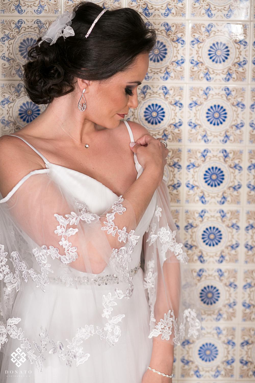 noiva arruma seu vestido em frente aos azolejo português da sala da noiva da fazenda.