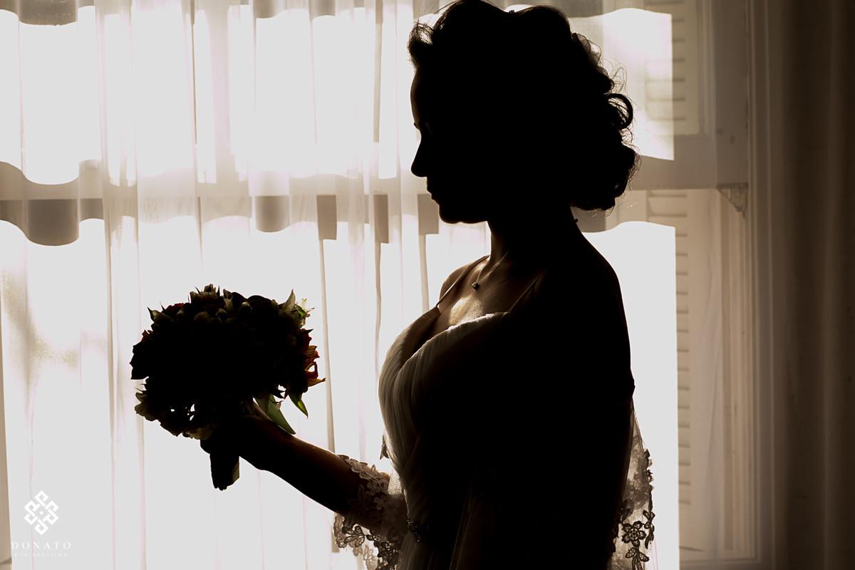 foto da noiva em seu momento antes do casamento, a imagem foi feita em frente a janela da fazenda 7 lagoas, deixando a noiva em silhueta.