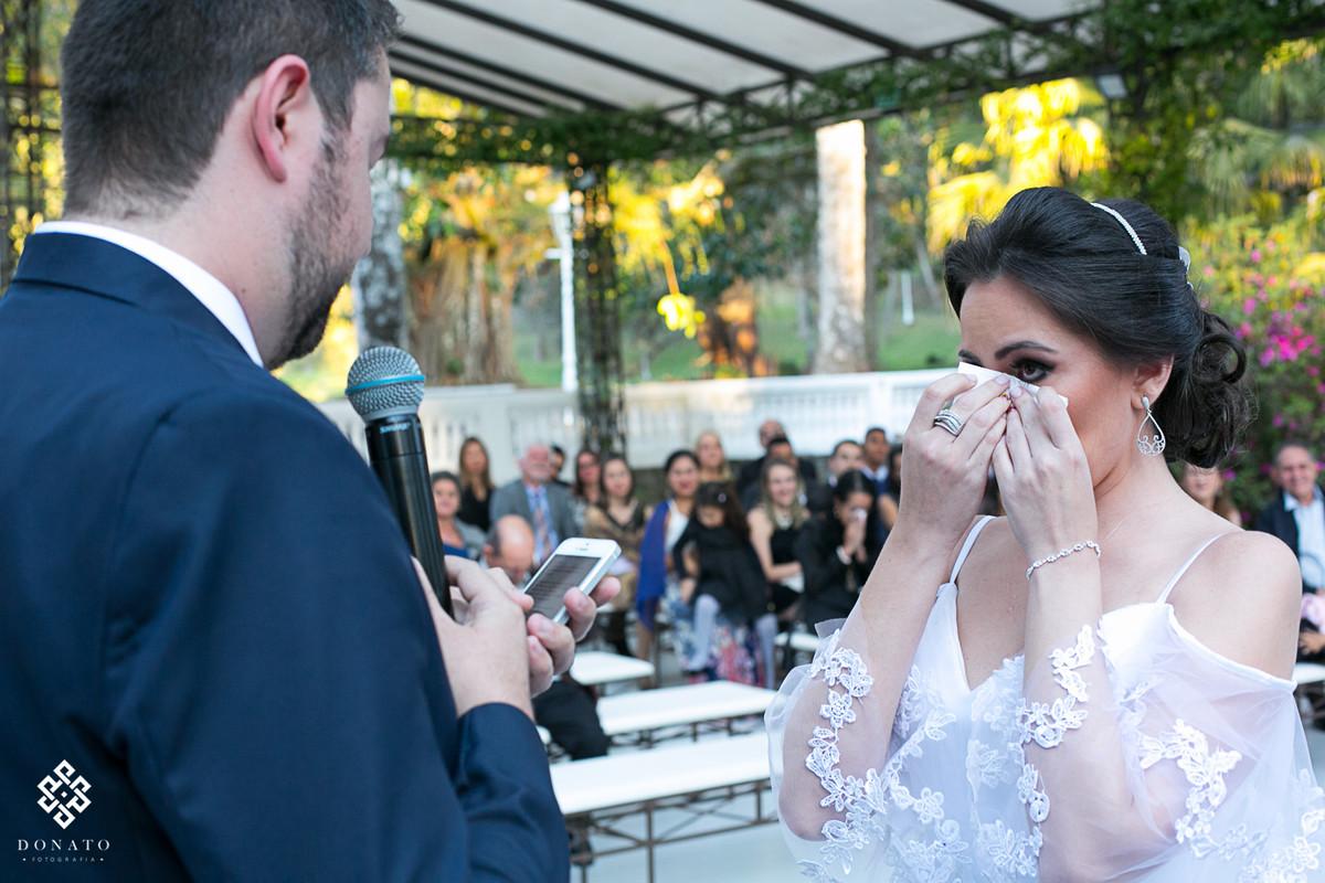 noiva enxuga as lagrimas após o noivo ler seus votos, a imagem é emocionante.