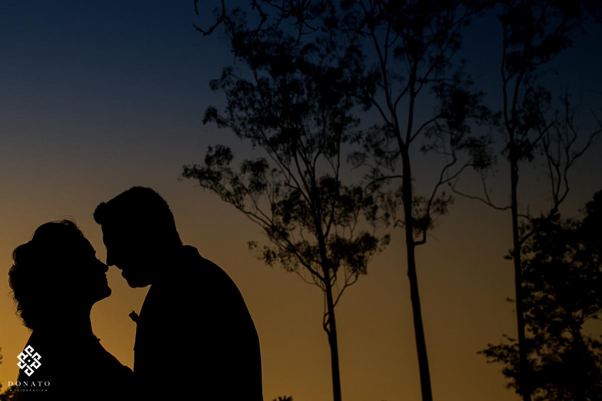 Noivos se beijam, a imagem esta em silhueta, e o céu esta azul e amarelo, muito lindo o seu de Arujá-SP.