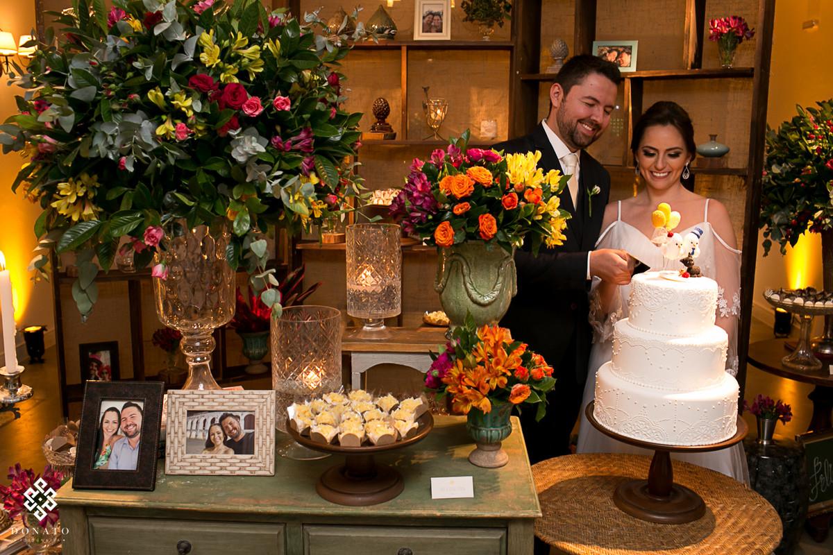 noivos brindam em frente a mesa de bolos e a linda estante de detalhes.