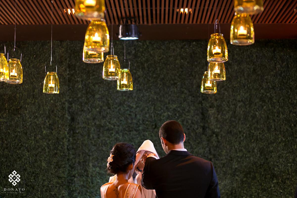 Visão de tr;ás do altar, na benção das alianças e o teto cheio de luz de velas.