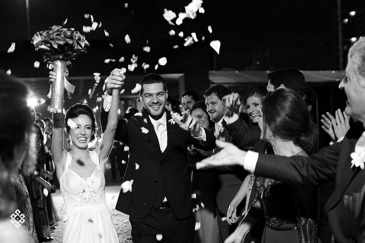 Padrinhos jogam pétalas de rosas na saída dos noivos.