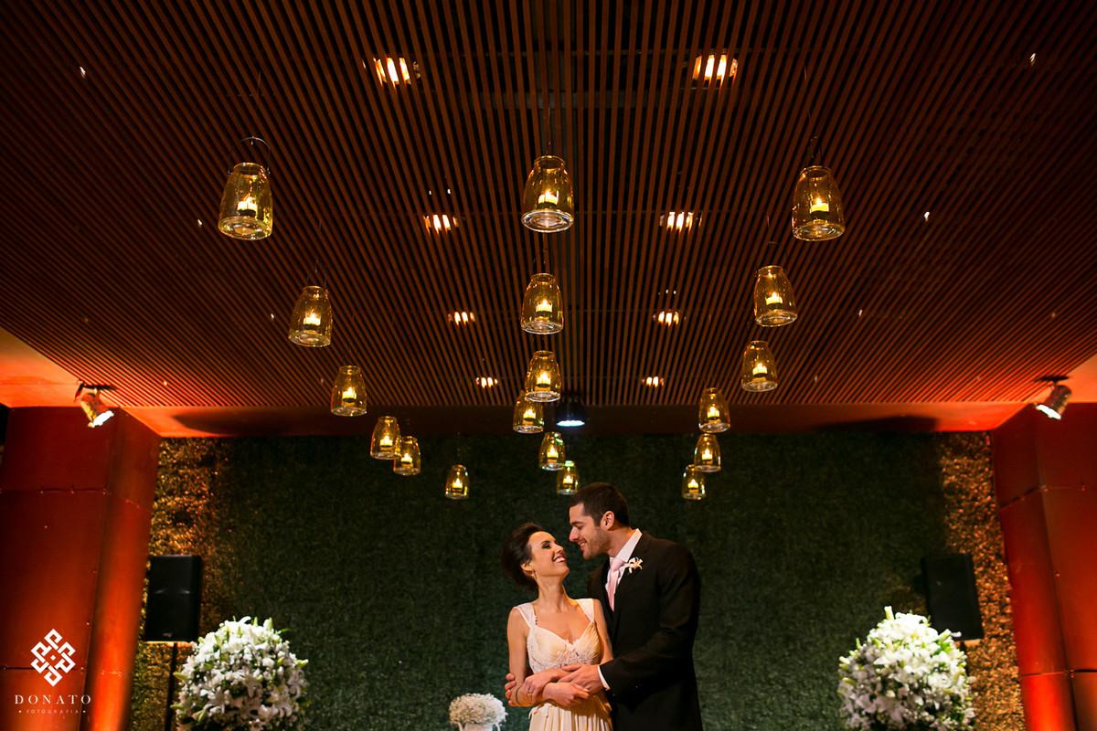 Foto dos noivos posada entre o teto de velas, linda decoração.
