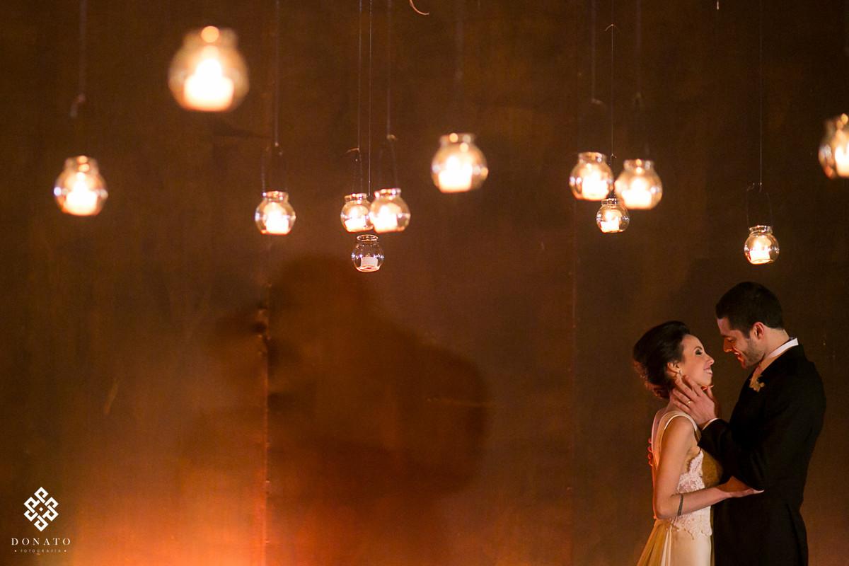 noivos se beijam entre as luz das velas da decoração da Casa Aragon.