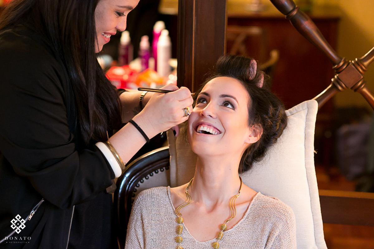Noiva faz maquiagem e sorri alegre e ansiosa.
