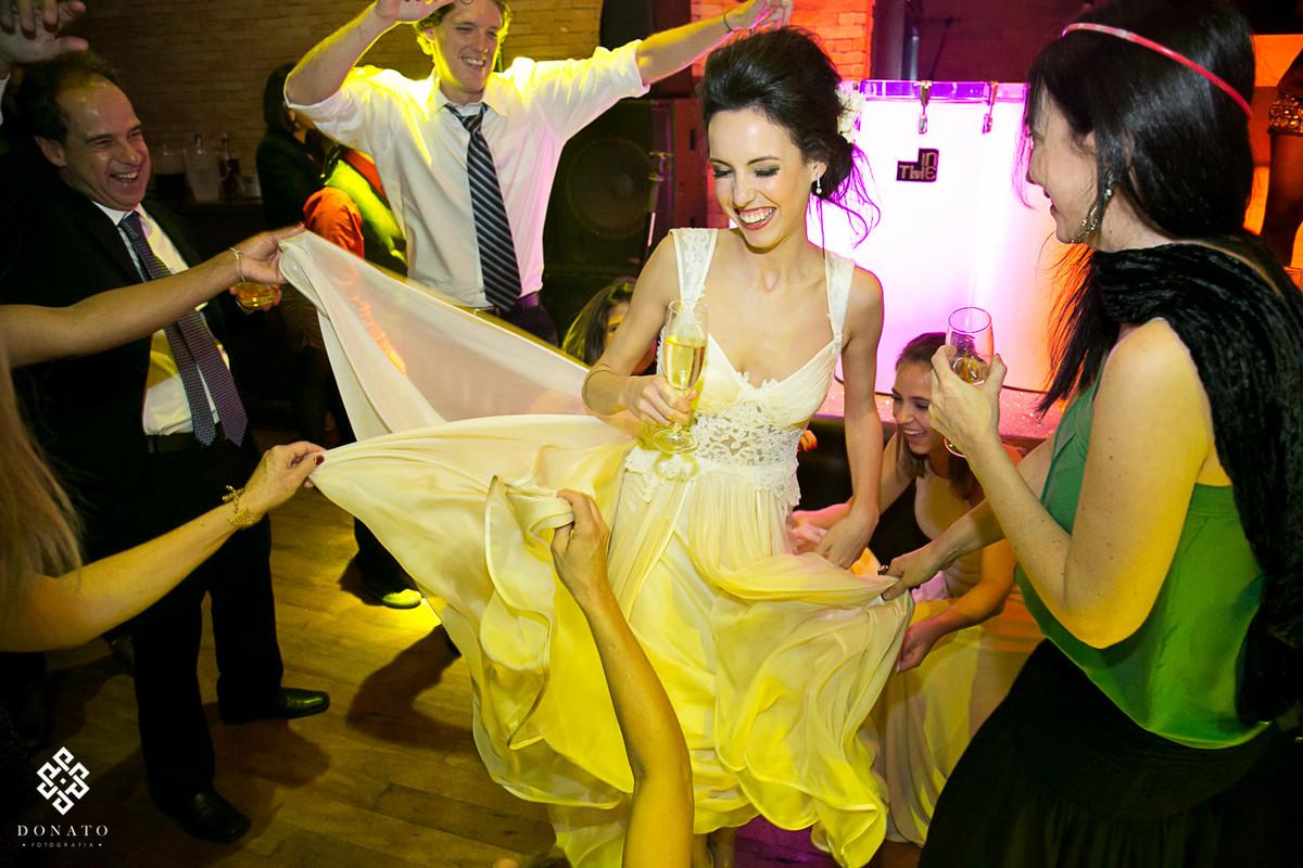 noiva dnaça e amigas pegam nas bordas do vestido lindo feito pela Fernanda Guedes.