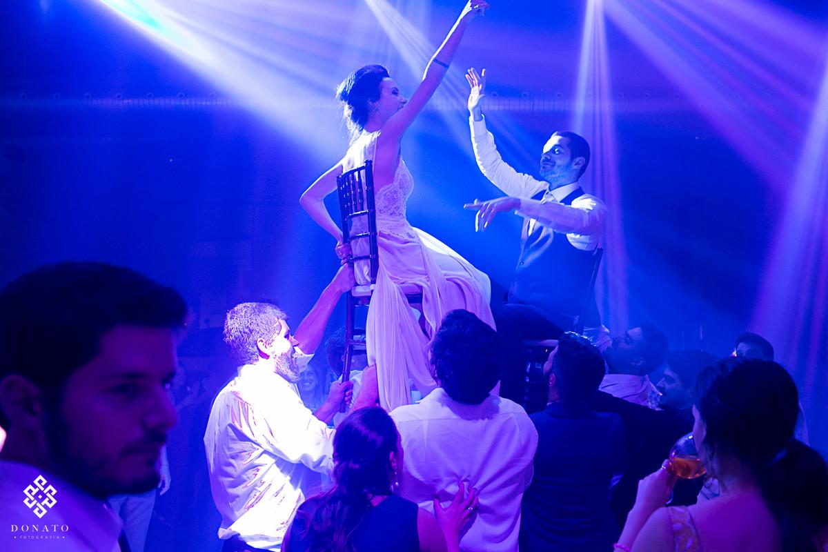 noiva e noivo são levantados em cadeiras, e dançam quase tocando o teto do salão do aragon.
