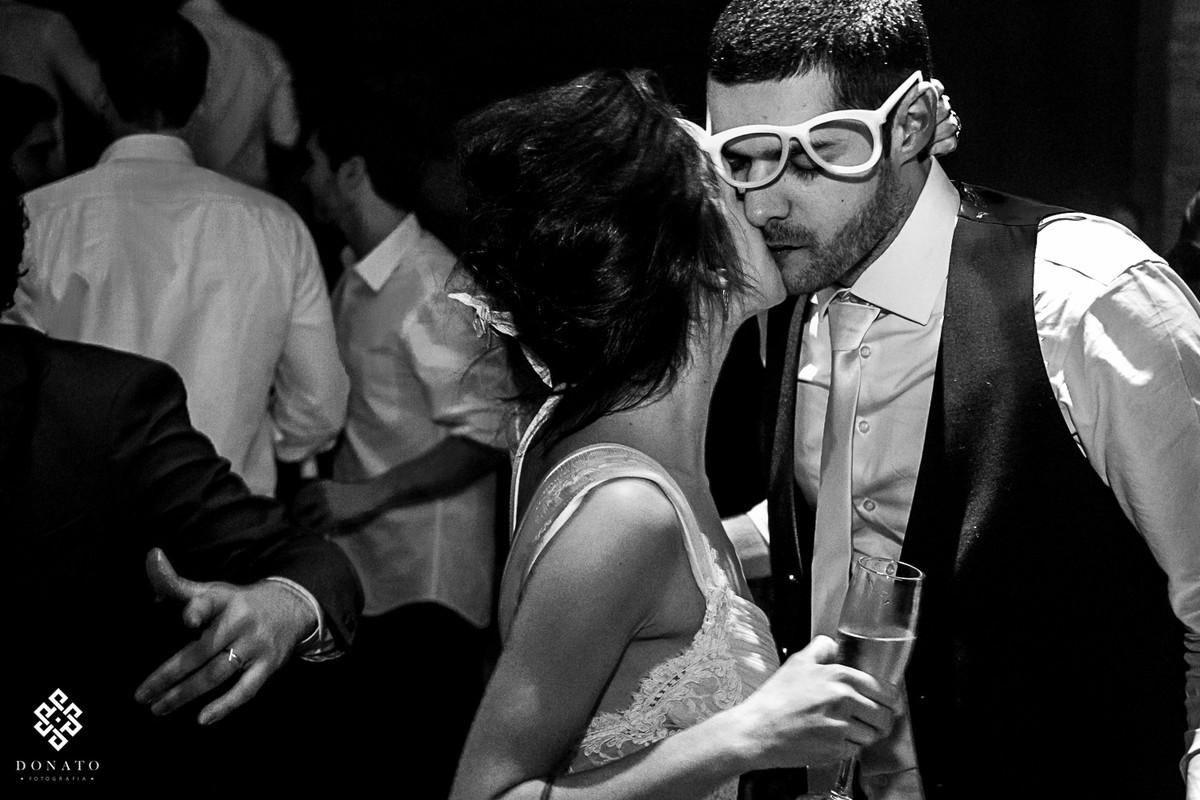 noiva beija o noivo, o óculos dela se desloca da cara, tornando assim a imagem muito divertida.