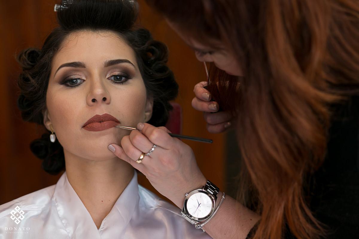 a maquiadora Evelyn conversani, retoca os detalhes do batom da noiva.
