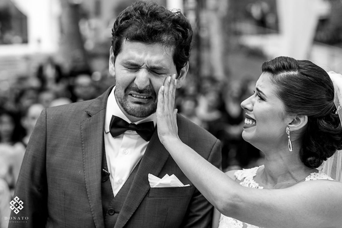 Foto emocionante, com a noiva secando as lagrimas do rosto do noivo.