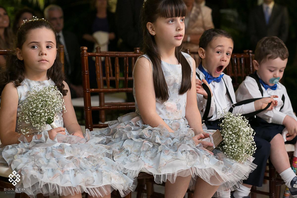 Pajem abre a boca com sono, enquanto as daminhas prestam atenção na cerimonia.