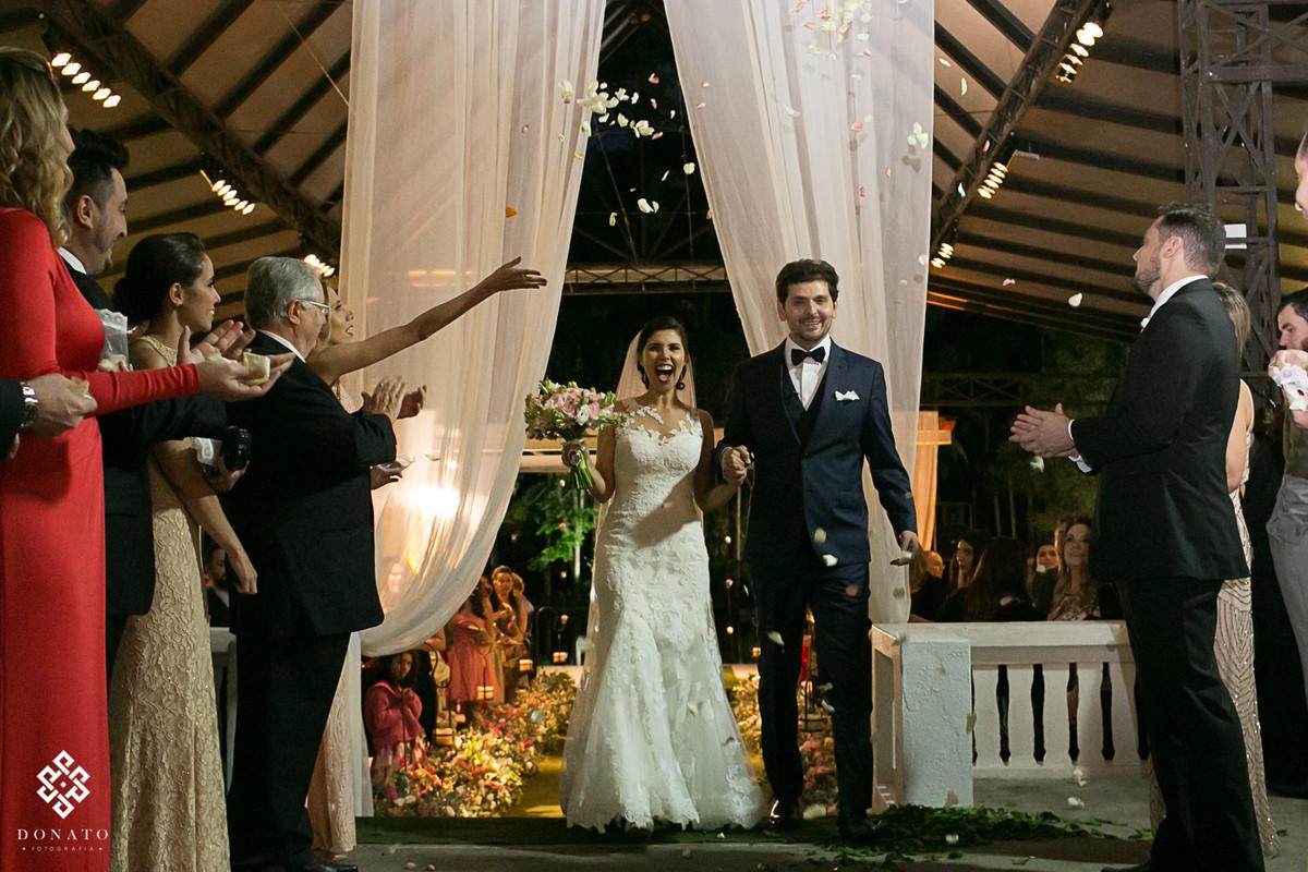 Noivos saem sorridentes da cerimonia, os padrinhos jogam pétalas de flores.