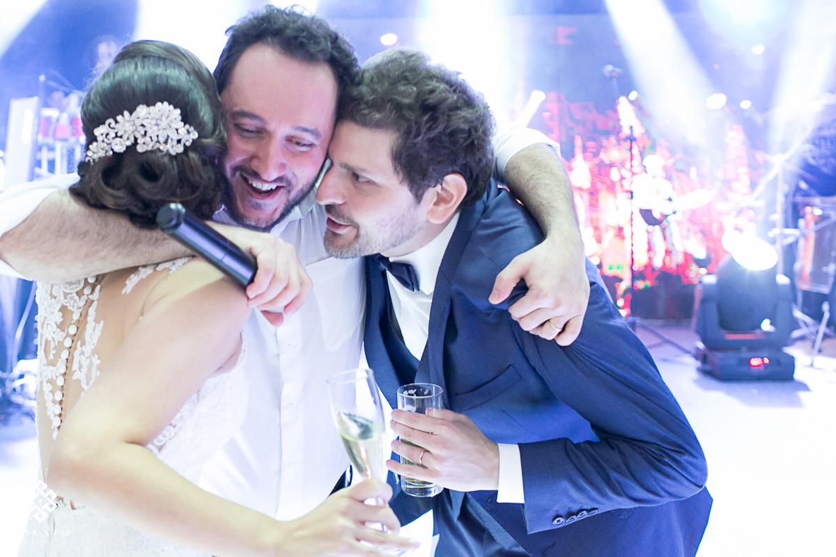 noivos abraçam o vocalista da banda kubalibre.
