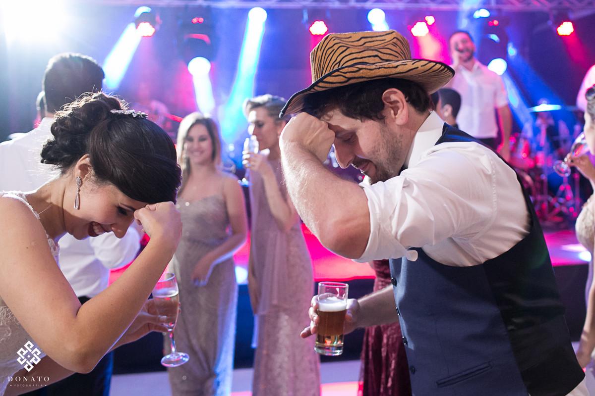 noivo dança com chapéu na pista de dança.