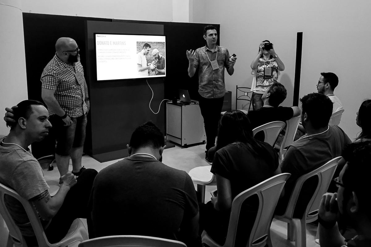 Leandro apresenta enquanto aparece na imagem a Tatiane braga fotografando e o Andre Martins olhando.