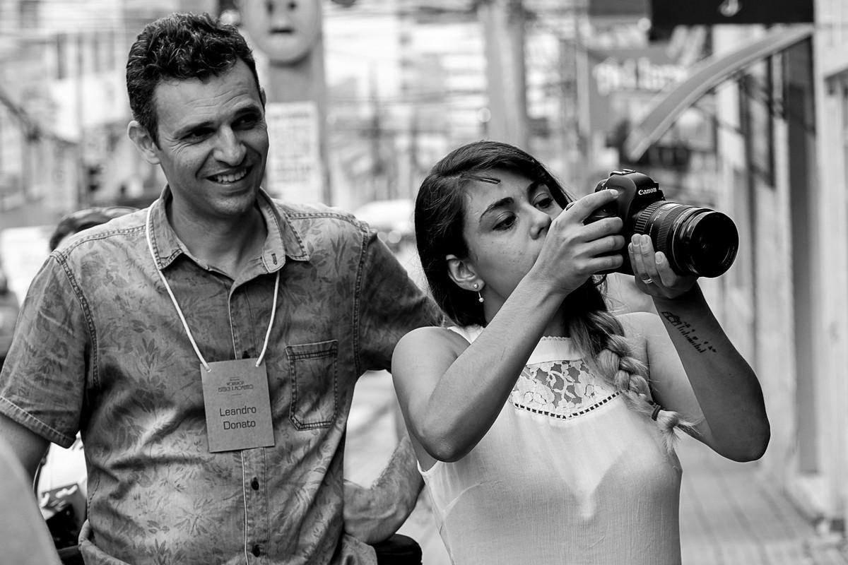 Leandro Donato confere aluno fotografando.