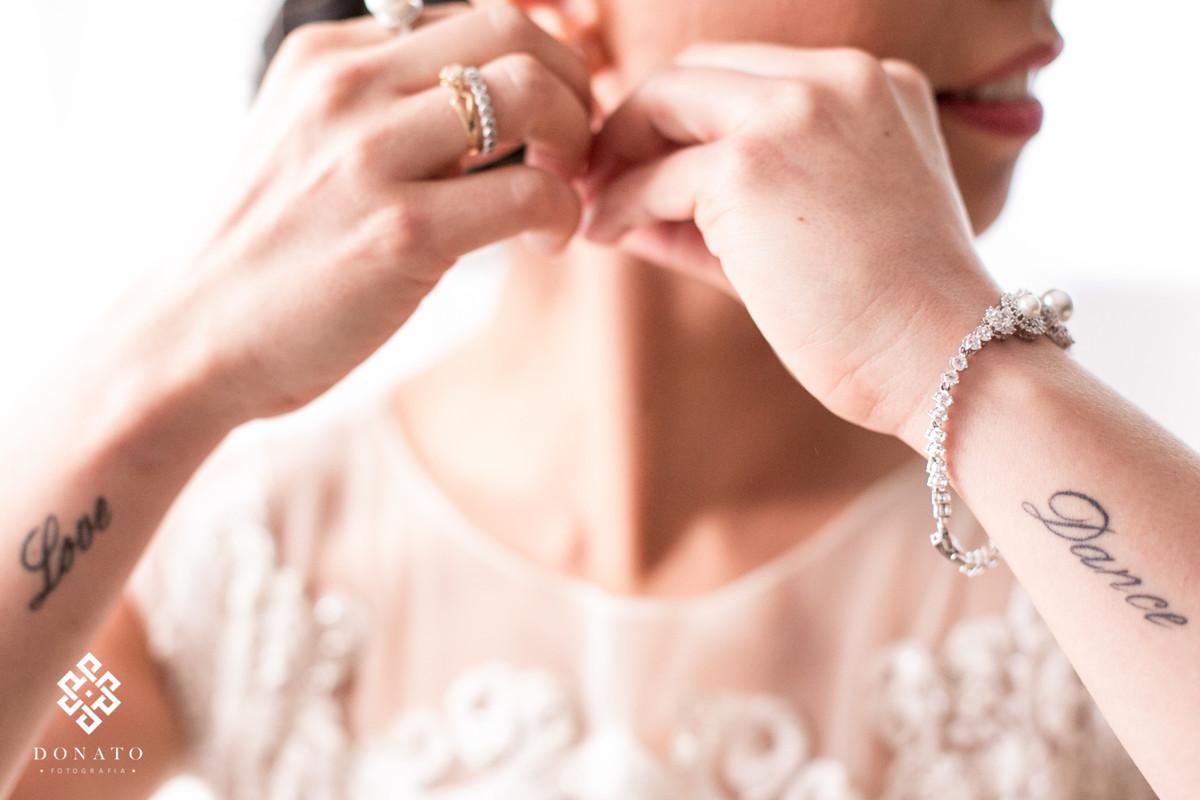 A noiva coloca os brincos, nesta foto da pra ver duas tatuagem que tem tudo haver com a noiva que é bailarina, onde esta escrito love e dance.