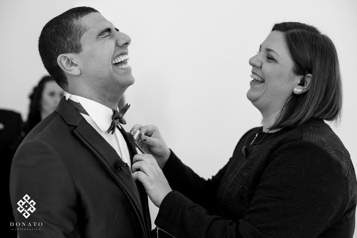 assessora arruma a gravata do noivo, ambos dão uma gargalhada muito divertida.
